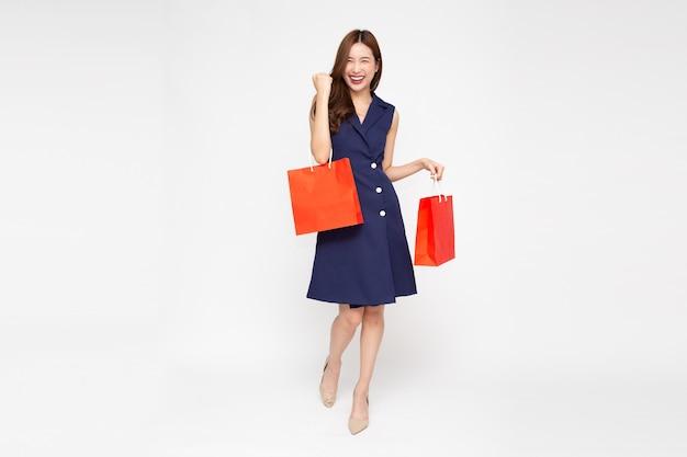 Azjatyckie kobiety trzymającej torby na zakupy w całym ciele na białym tle