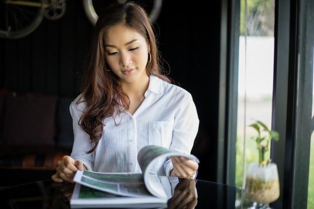 Azjatyckie kobiety uśmiecha się książkę dla relaksu przy sklep z kawą i czyta