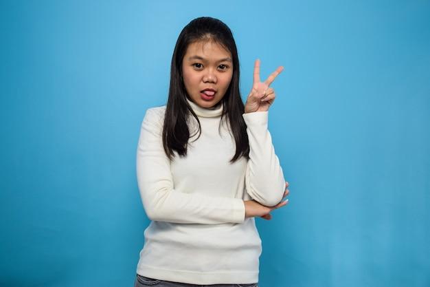 Azjatyckie kobiety używające białej koszulki odizolowanej na niebiesko pokazującej znak pokoju i uśmiechniętego znaku zwycięstwa