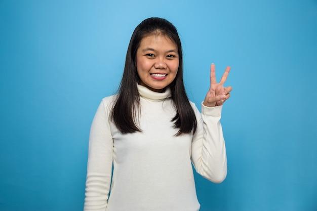 Azjatyckie kobiety używające białej koszulki z niebieskim odosobnionym tłem pokazującym znak pokoju i uśmiechniętym