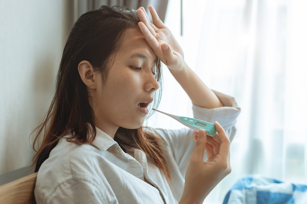 Azjatyckie kobiety używające doustnego termometru testowego mierzą temperaturę ciała w celu zdiagnozowania grypy w wyniku zakażenia koronawirusem.