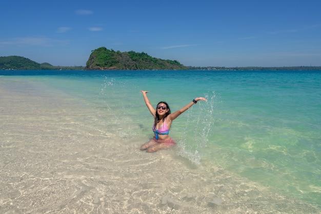 Azjatyckie kobiety w bikini bawiące się w błękitne morze z rozpryskiwaniem się na plaży na wyspie, szczęśliwa dziewczyna na wakacjach w lecie na plaży na wyspie rayang, rayong, tajlandia