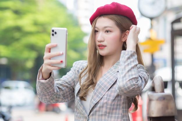 Azjatyckie kobiety w brązowych włosach robi zdjęcie selfie przez smartfon na ulicy jako tło.