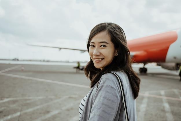 Azjatyckie kobiety w ciąży ciągnie walizki podczas gdy chodzący na pasie startowym