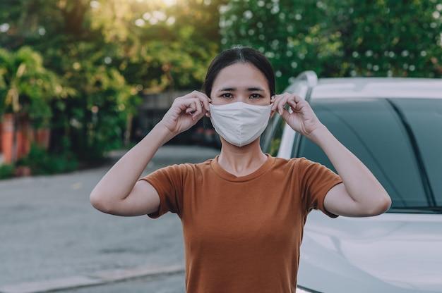 Azjatyckie kobiety w masce stojącej na zewnątrz samochodu