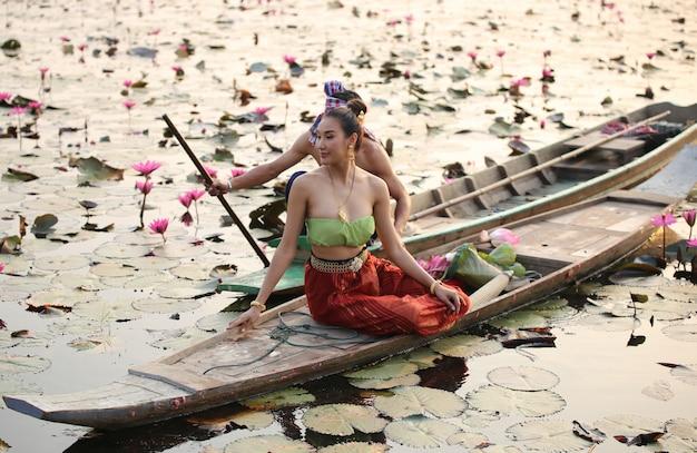 Azjatyckie kobiety w tajlandia tradycyjnej kostiumowej siedzącej łodzi w lotosowym jeziorze