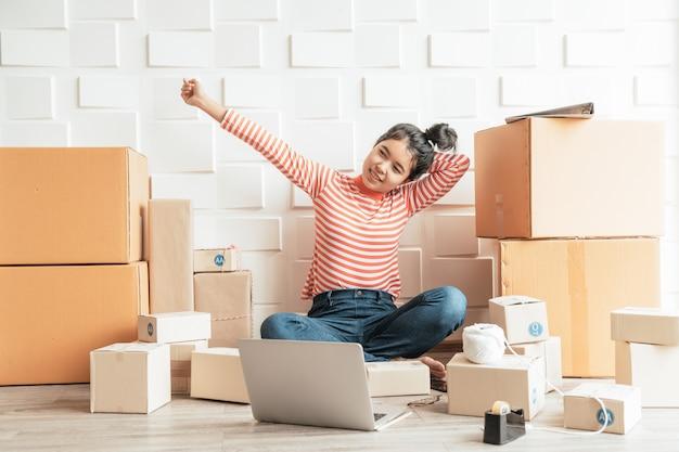 Azjatyckie kobiety właściciel firmy pracuje w domu z pudełkiem pakowania w miejscu pracy