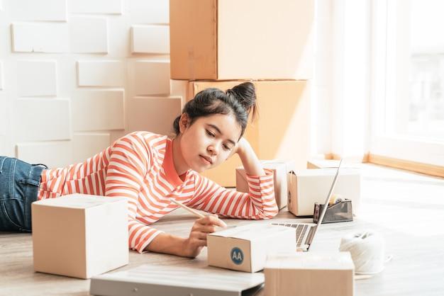 Azjatyckie kobiety właścicielki firmy pracującej w domu z opakowaniem w miejscu pracy - zakupy online przedsiębiorca mśp lub koncepcja sprzedaży online