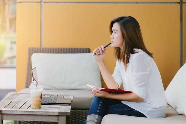 Azjatyckie kobiety woking przy kawiarnią z laptopem myśleć biznesową projekt akcję