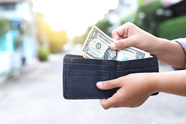 Azjatyckie kobiety wyciągając pieniądze z czarnej torebki do wydania.