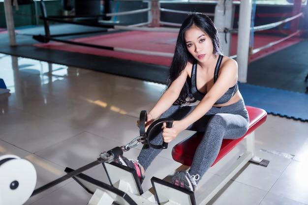 Azjatyckie kobiety wykonuje robić ćwiczeniom trenuje z wioślarską maszyną