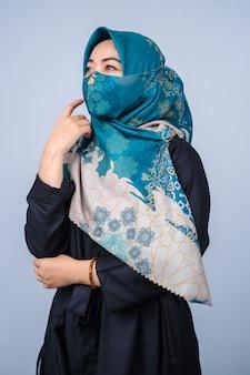 Azjatyckie kobiety z hidżabem i modną maską na twarz pozują do kamery na szarym tle