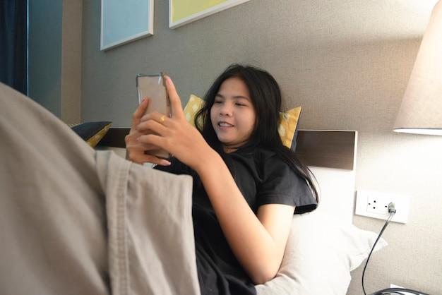 Azjatyckie kobiety z używać smartphone w sypialni z ciemnym pokojem.