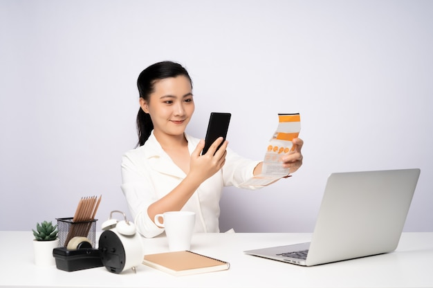 Azjatyckie kobiety za pomocą inteligentnego telefonu zeskanować kod qr dla płatności za narzędzie do rozliczeń online.