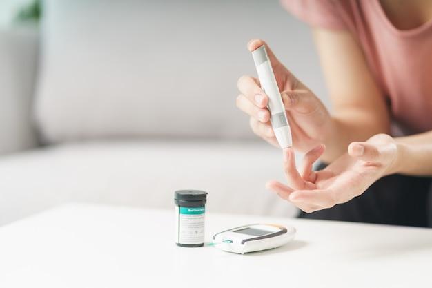 Azjatyckie kobiety za pomocą lancetu na palcu do sprawdzania poziomu cukru we krwi przez glukometr, opieka zdrowotna i medycyna, cukrzyca, koncepcja glikemii