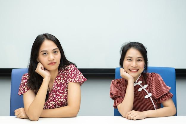 Azjatyckie ładne kobiety w chińskim stylu cheongsam wielka szczęśliwa radosna i wspólna dyskusja w sali konferencyjnej w biurze z radością i uśmiechem