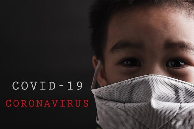 Azjatyckie małe dziecko jest ubranym ochronną maskę na wybuch koronawirusa