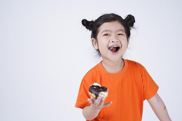 Azjatyckie małe słodkie dziewczyny jedzenie duży pączek na białym tle