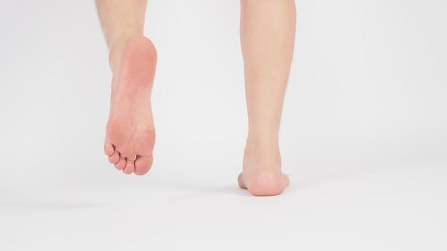 Azjatyckie męskie nogi i boso są izolowane na białym tle