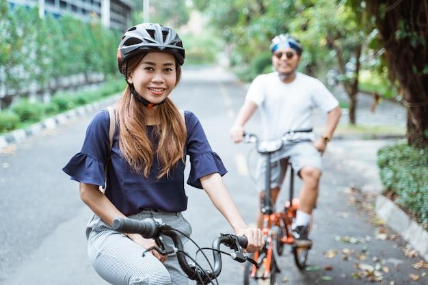 Azjatyckie młode pary w hełmach wspólnie jeżdżą na rowerach