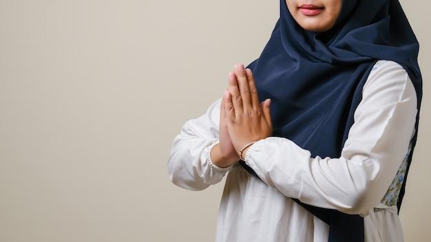 Azjatyckie muzułmanki noszące hidżab uśmiechające się do kamery i gestykulujące witając gości na eid mubarak lub eid fitr lub eid al-fitr