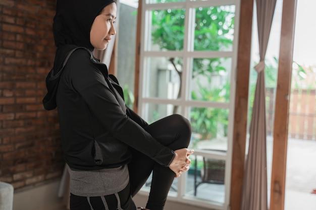 Azjatyckie muzułmańskie kobiety jest ubranym hijab sportswear robi nóg rozciągać