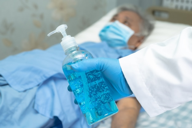 Azjatyckie mycie rąk przez naciśnięcie niebieskiego alkoholu żel do dezynfekcji w celu ochrony wirusa covid-19.