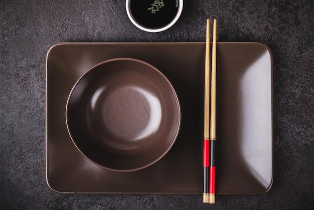 Azjatyckie nakrycie stołu. brązowe miski, sos sojowy i pałeczki bambusowe.