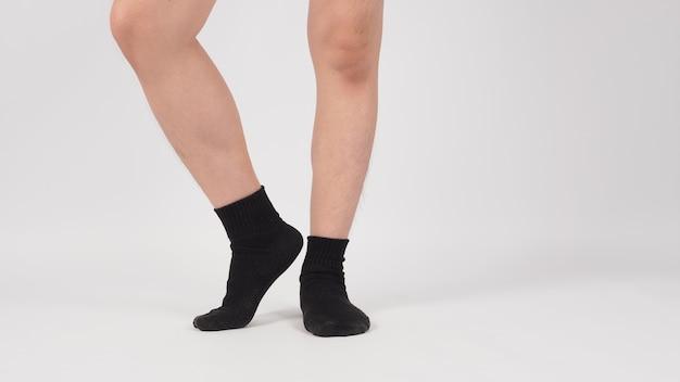 Azjatyckie nogi i stopy nosić czarne skarpety na białym tle. odosobniony