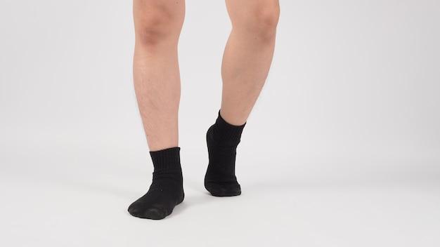Azjatyckie Nogi I Stopy Nosić Czarne Skarpety Na Białym Tle. Odosobniony Premium Zdjęcia