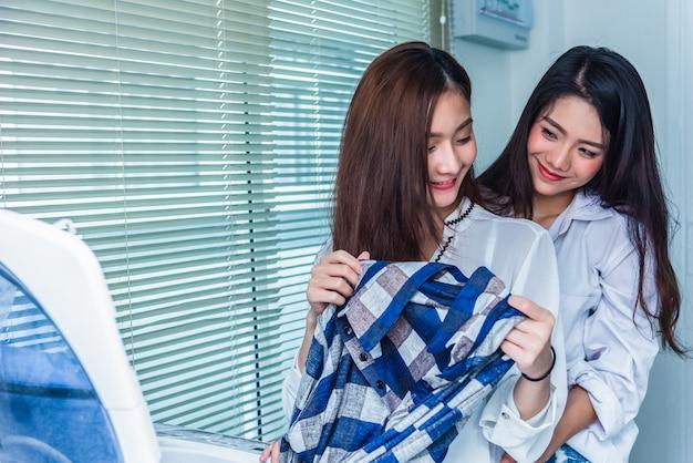 Azjatyckie par kobiety robi sprzątaniu i obowiązkom przed pralką