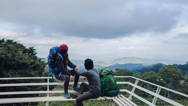 Azjatyckie pary podróżują naturę na górach w zimie.