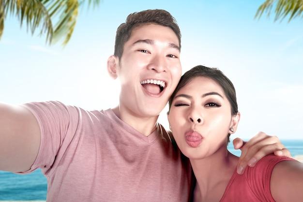 Azjatyckie pary robią sobie selfie ze śmieszną miną na plaży z widokiem na błękitne niebo