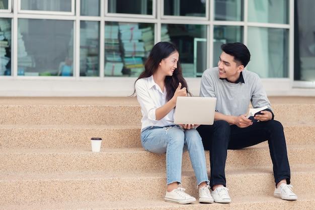 Azjatyckie pary studentów lub kolegów siedzących przy schodach i uśmiechniętych jak używają laptopa