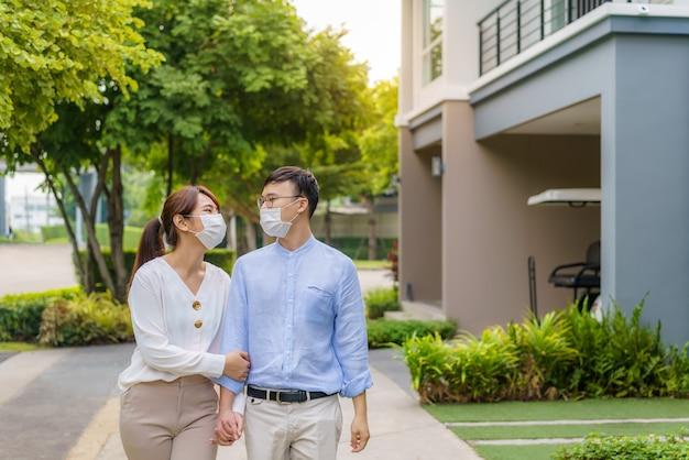 Azjatyckie pary w maskach ochronnych spacerują razem ścieżką w parku publicznym w wiosce podczas epidemii koronawirusa