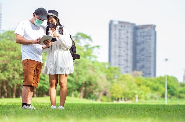 Azjatyckie pary z maską na twarz szukają informacji turystycznych za pomocą tabletów z niesamowitymi miejscami do odwiedzenia w mieście z tłem budynków i parków. koncepcja technologii i podróży. nowy normalny motyw