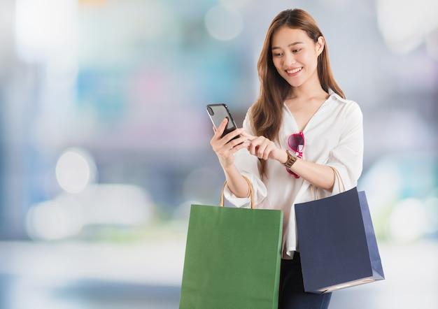 Azjatyckie piękne kobiety blogger używają smartfona, zakupy online z torbą na zakupy w niewyraźne tło wnętrza centrum handlowego. koncepcja biznesu zakupów online.