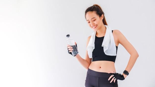 Azjatyckie piękne kobiety trzymając butelkę wody po zabawie jogi i ćwiczeń na tle białej ściany z miejsca na kopię.