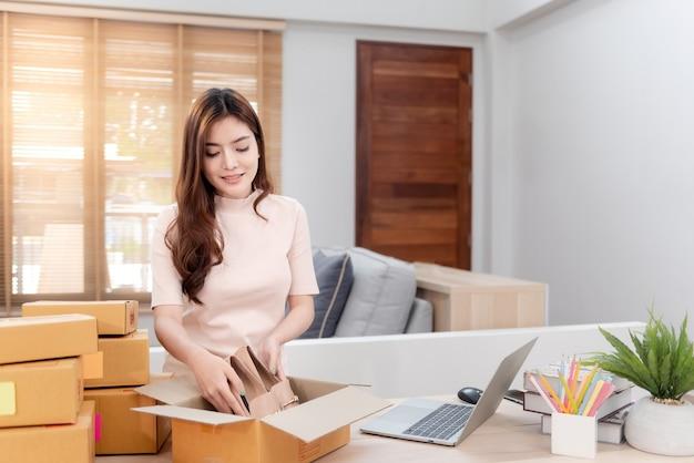 Azjatyckie piękno sprawdzanie zamówienia laptopa przez internet.