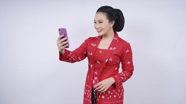 Azjatyckie piękno w kebaya selfie na smartfonie na białym tle