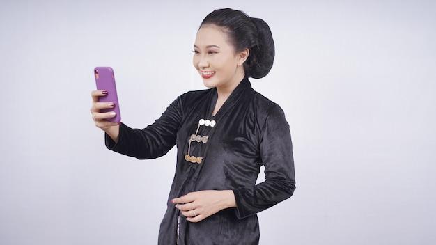 Azjatyckie piękności w kebaya bawiące się telefonem komórkowym na białym tle