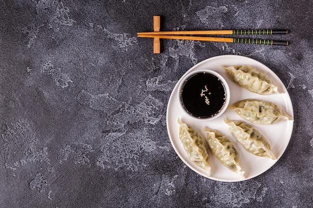 Azjatyckie pierogi, sos sojowy, pałeczki, widok z góry
