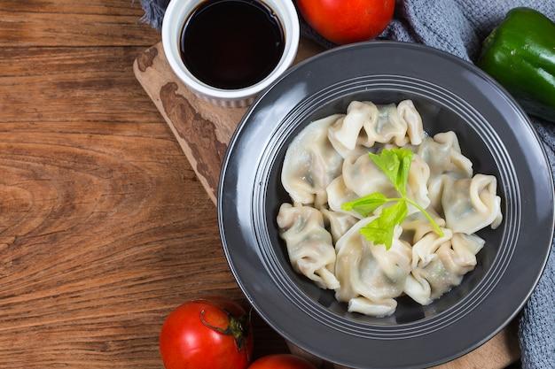 Azjatyckie pierogi w misce, pałeczki, chińskie pierogi na kolację.
