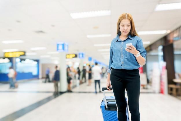 Azjatyckie podróżnicze kobiety patrzeje lot w smartphone przy lotniskowym terminal podróżuje pojęcie