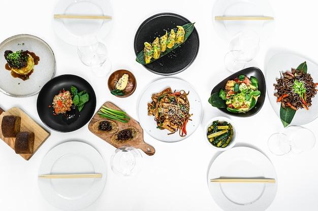 Azjatyckie potrawy serwowane na białym stole. zestaw do kuchni chińskiej i wietnamskiej