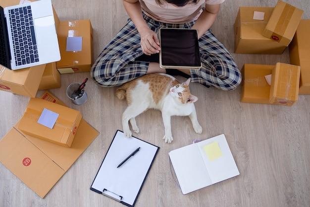 Azjatyckie przedsiębiorczynie i sprzedaż internetowa. kobieta jest samozatrudniona, pracuje w domu z właścicielem małej firmy. dostawa opakowań i marketing online dla mśp