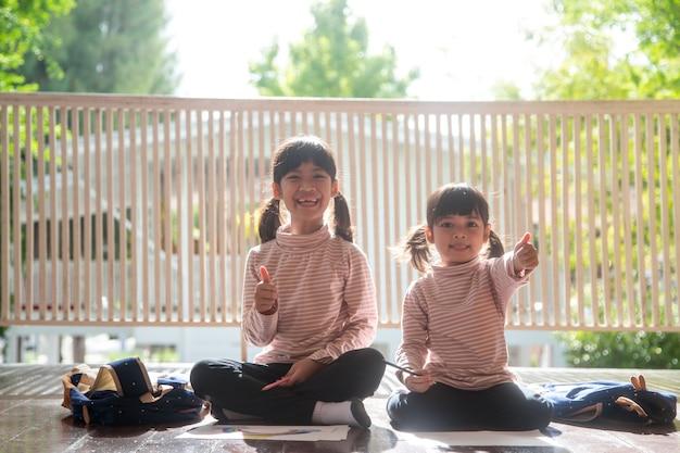 Azjatyckie rodzeństwo dzieci rysujące i malujące kolorowanki na papierze