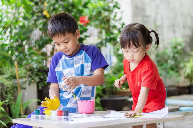 Azjatyckie rodzeństwo rysuje i maluje kolorowanki na papierze w pokoju.