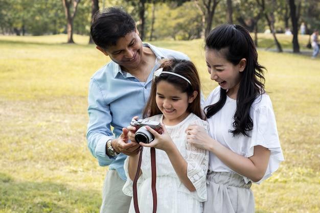 Azjatyckie rodziny oglądają zdjęcia ze swoich aparatów.