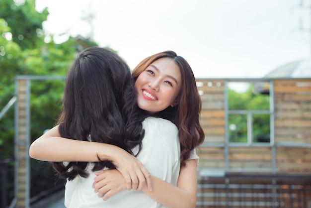 Azjatyckie siostry przytulają się i uśmiechają w parku.